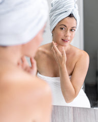 A woman in a towel applying some skincare products to her face.