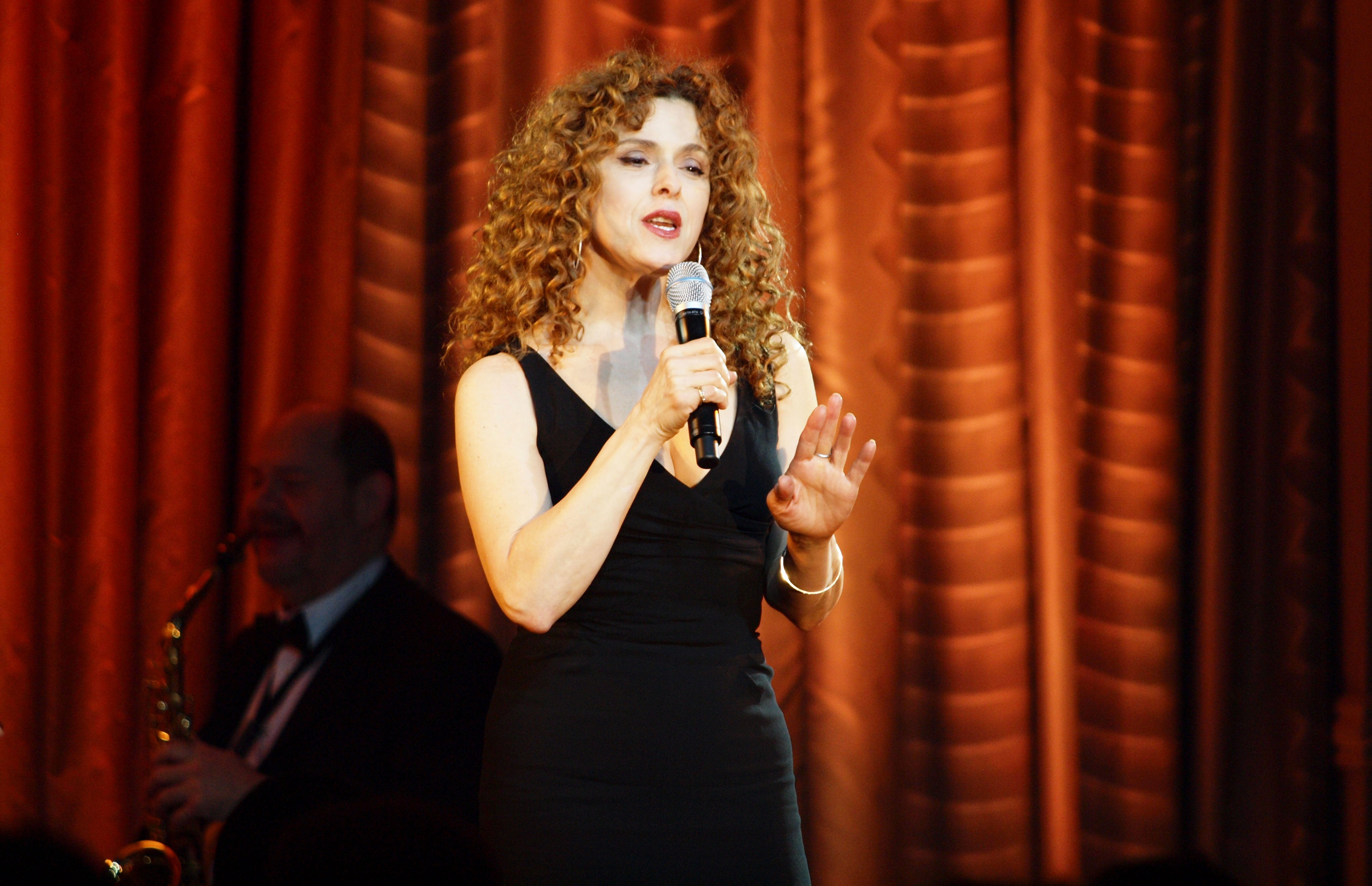 Bernadette Peter holding a mic wearing a black dress on a stage
