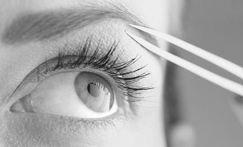 Woman's eyes with tweezers in the position to pluck her eyebrow.