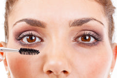 Women with mascara brush getting ready to apply mascara.