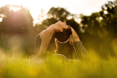 A woman doing yoga in a field. Her feet are on touching the top of her head.