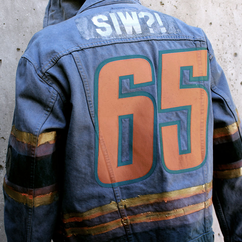 Model wearing of Stick It Wear?! 'No 65' Custom Hockey Style Denim Jacket in blue with jersey numbers.