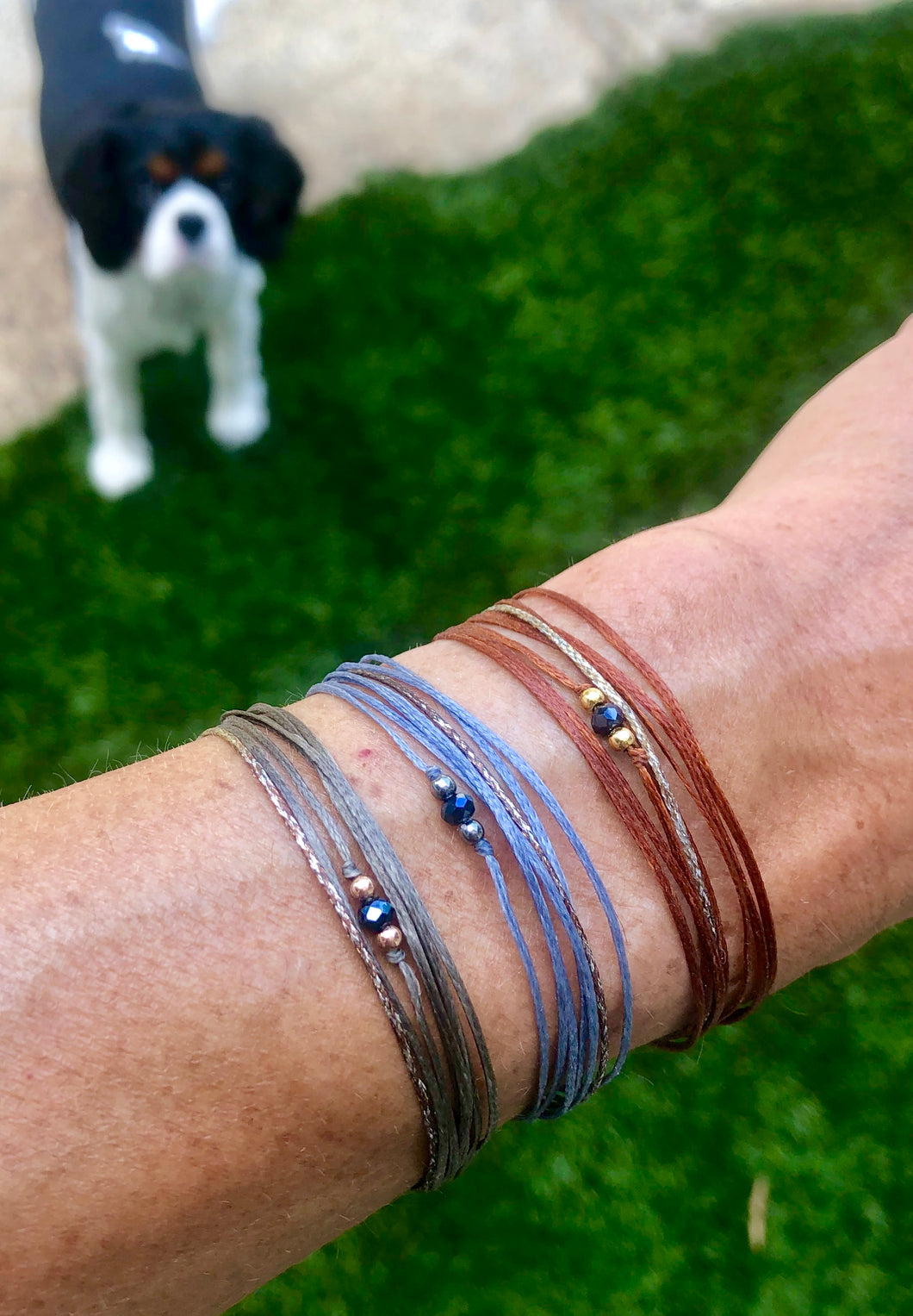 Left to right: rose gold vermeil featured in taupe, rhodium sterling silver, featured in grey yellow gold vermeil featured rust; all with sparkly silver-brown cord
