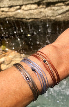 Load image into Gallery viewer, Left to right: rose gold vermeil featured in taupe, rhodium sterling silver, featured in grey yellow gold vermeil featured rust; all with sparkly silver-brown cord