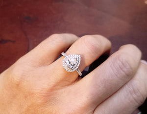 Pear shaped halo diamond engagment ring on the finger