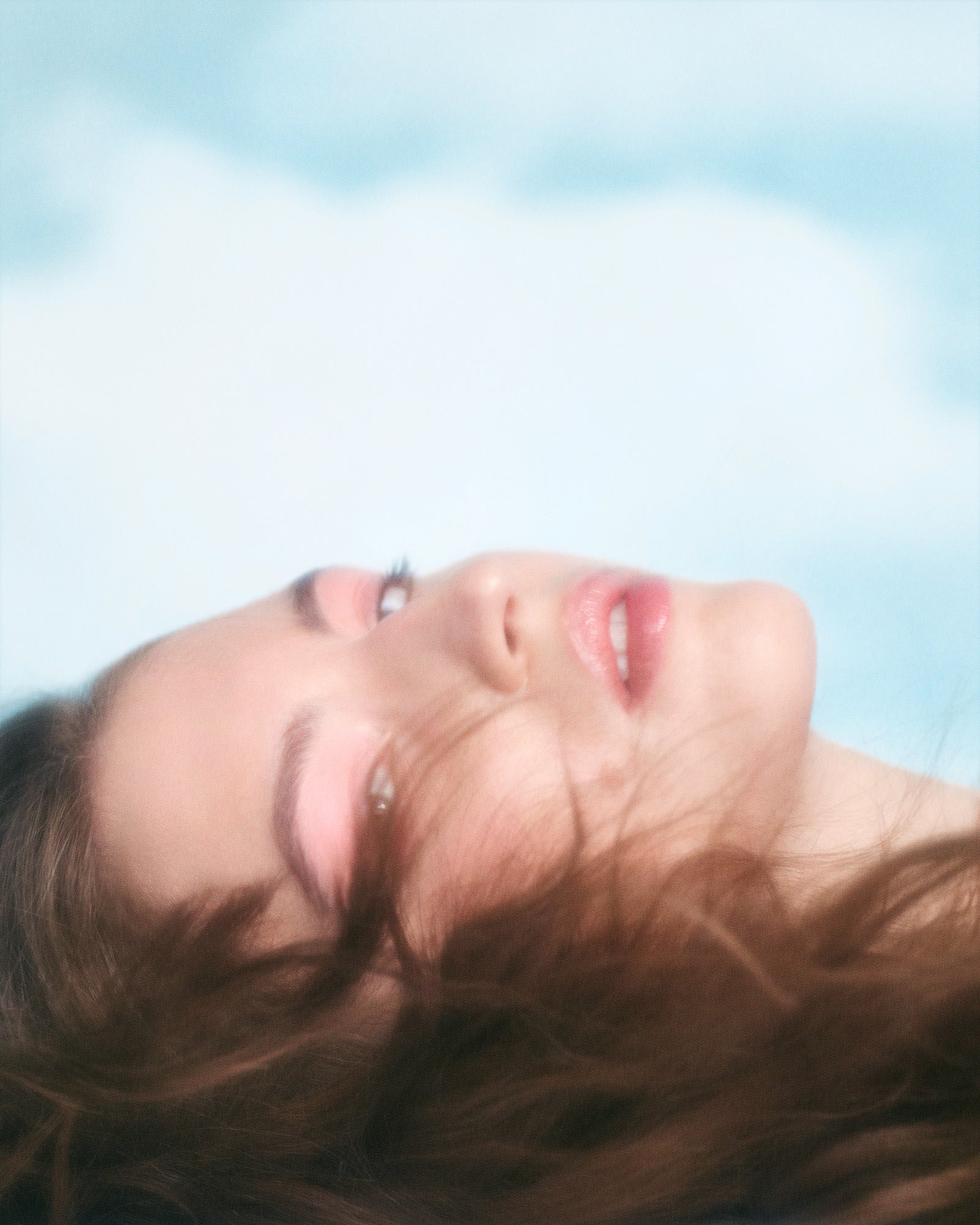 woman laying under clouds
