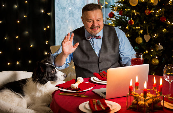 man and dog enjoying christmas dinner and video call with family