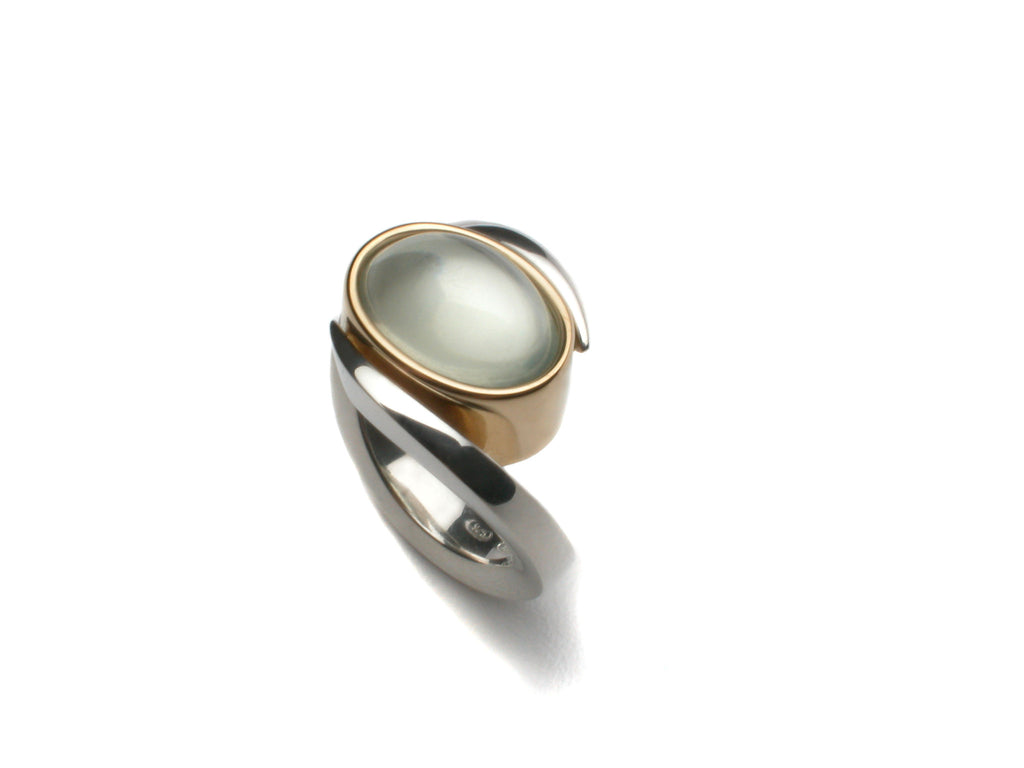 Sterling silver and eighteen karat yellow gold holding an oval Moonstone cabochon. Price inquiry. $0.00