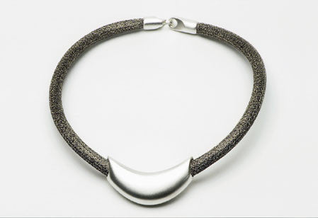 Necklace in sterling silver with a tubular puzzle clasp on steel mesh cord. $720.00