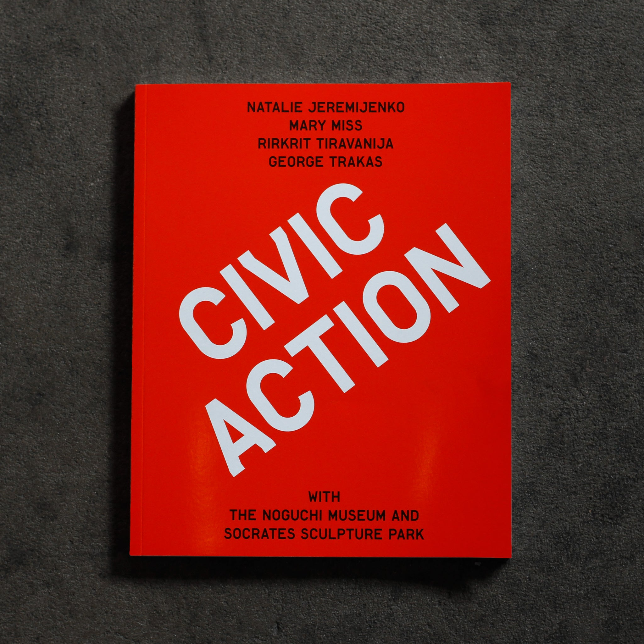 Cover of 'Civic Action,' a bright red-orange solid cover with large diagonal headline 'Civic Action' in white sans serif type, 'Natalie Jeremijenko, Mary Miss, Rikrit Tiravanija, George Trakas' in smaller centered black sans serif type at top and 'with The Noguchi Museum and Socrates Sculpture Park' in same black centered type at bottom