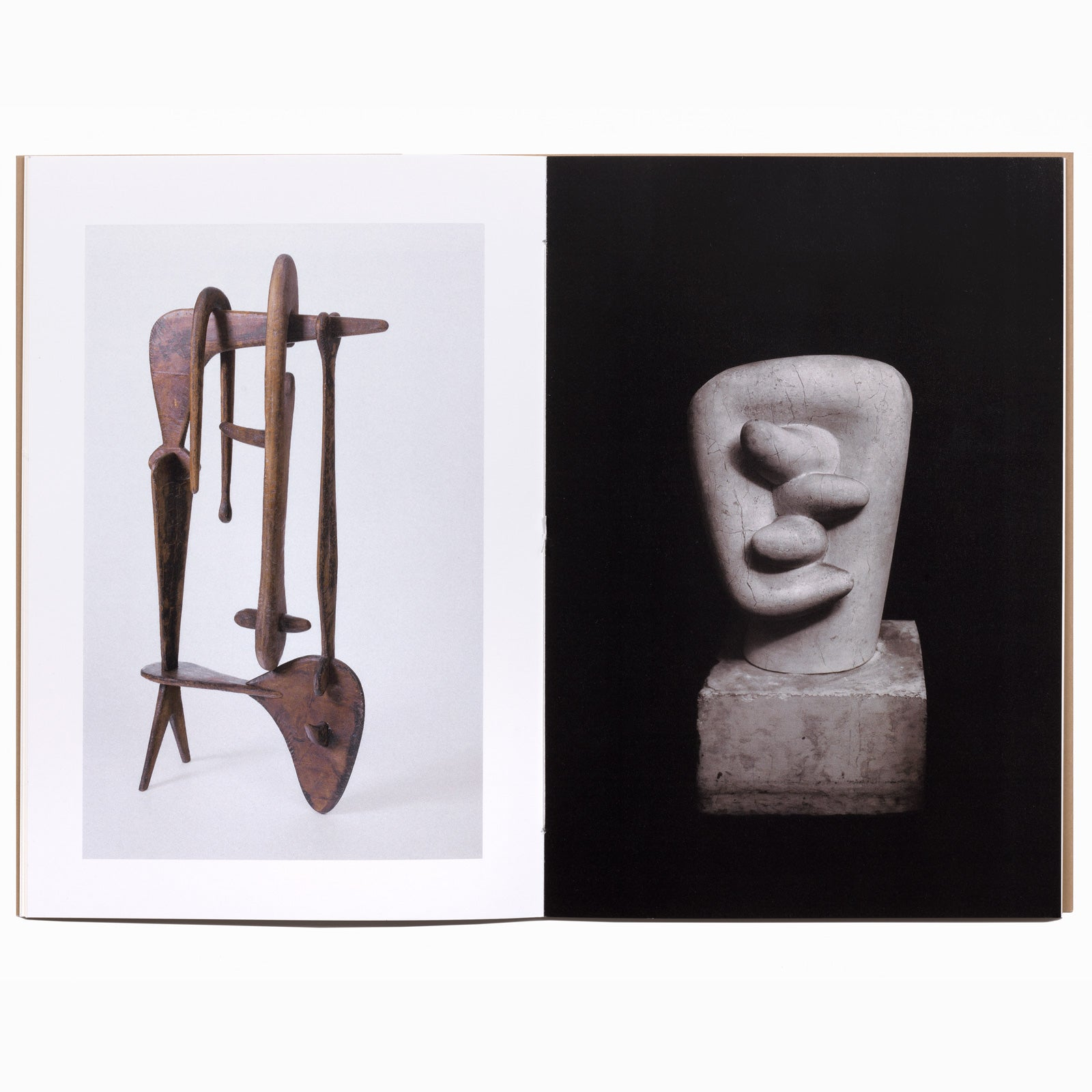 Image spread with Isamu Noguchi's mahogany wood interlocking sculpture 'Remembrance' on left on a light grey background with white frame, and white marble sculpture 'Noodle' on right with an intense black background. The book is hand bound with a subtle white thread knotted in the center of the page.