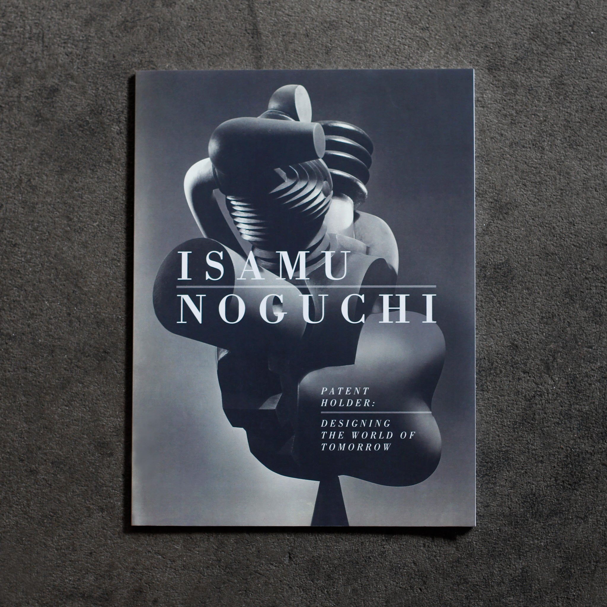 Cover of 'Isamu Noguchi, Patent Holder.' Detail photograph of Isamu Noguchi's 1000 Horsepower Heart, a plaster sculpture of a biomorphic engine. White headline text runs over the image, 'Isamu Noguchi' 'Patent Holder: Designing for the World of Tomorrow'