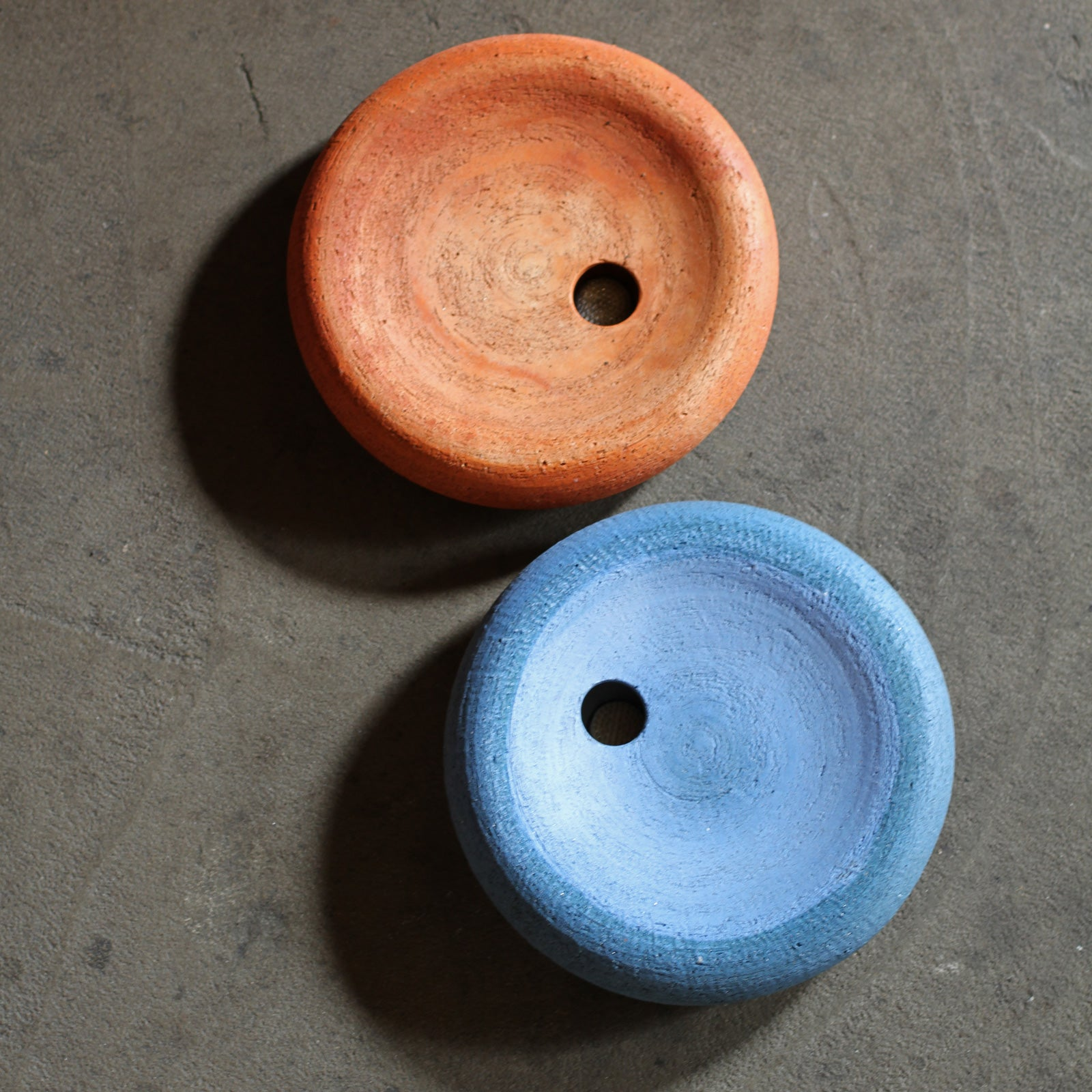 Two low round salt-fired clay ikebana vases with small round hole off-center, one orange and one cobalt blue