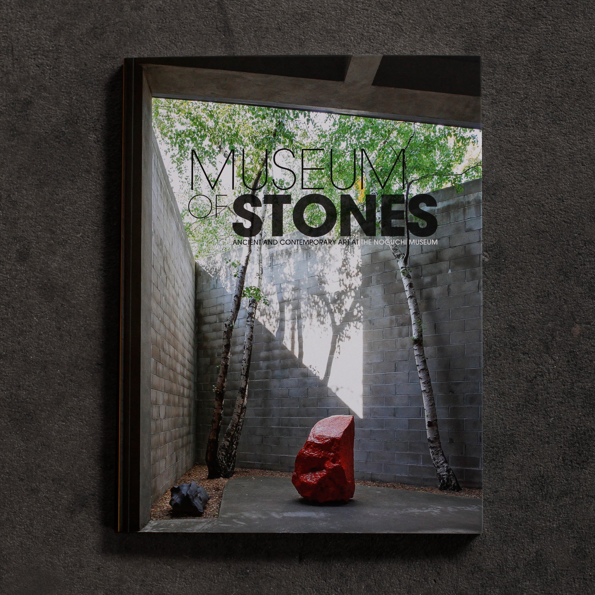 Museum of Stones cover. Bright red stone sculpture by Bosco Sodi stands between two birch trees in a beam of sunlight in the cutaway of the Noguchi Museum's Area 1