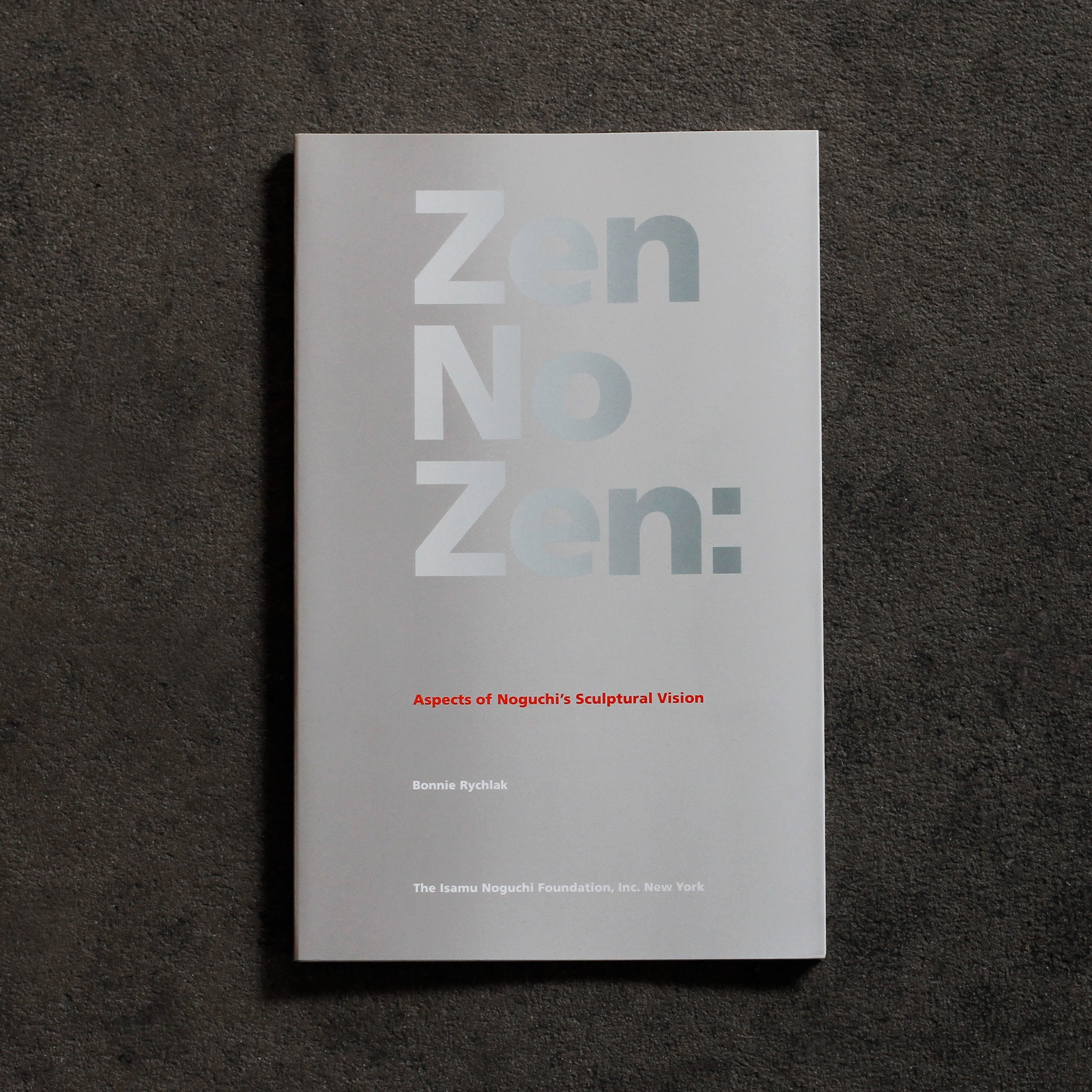 Cover of 'Zen No Zen.' Softcover book with silver grey background and large reflective silver bold sans serif headline text 'Zen No Zen'. In small red sans serif text below, 'Aspects of Noguchi's Sculptural Vision' and in white text below, same type style, 'Bonnie Rychlak,' 'The Isamu Noguchi Foundation Inc. New York'