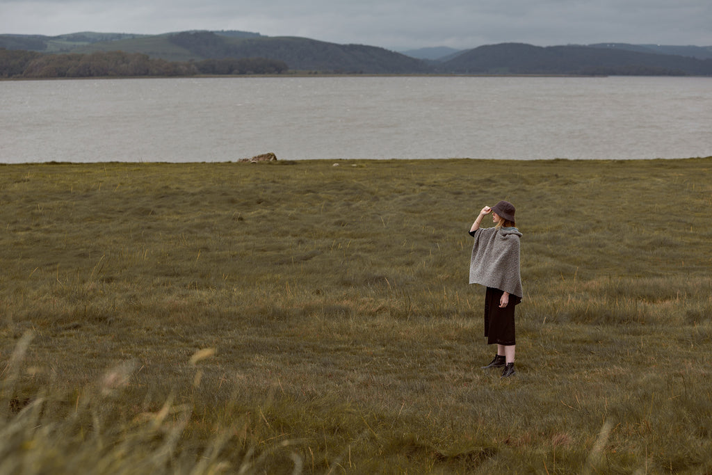 OUBAS model Holly stands in the foreground of Cumbria's landscape wearing grey and black knitwear