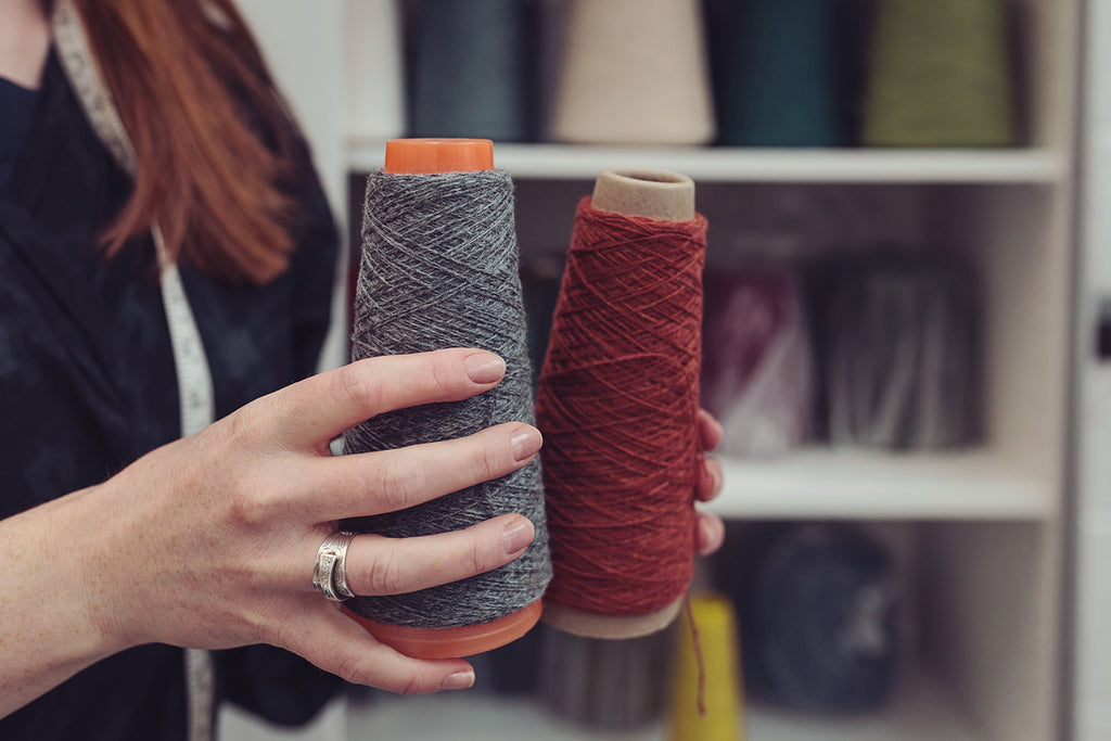 OUBAS founder Kate Stalker holds two cones of yarn in grey and maroon