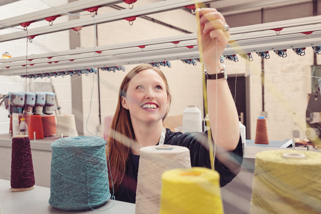 OUBAS founder Kate Stalker smiles as she monitors the industrial knitting machines in the studio