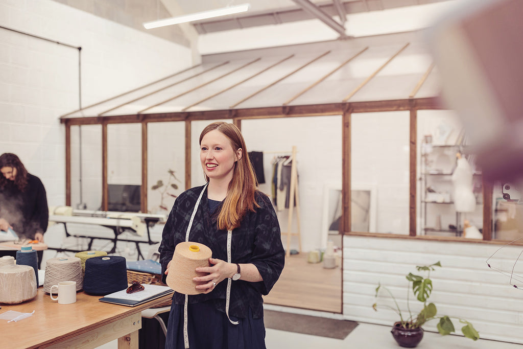 OUBAS founder Kate Stalker in the studio holding a cone of light coloured yarn