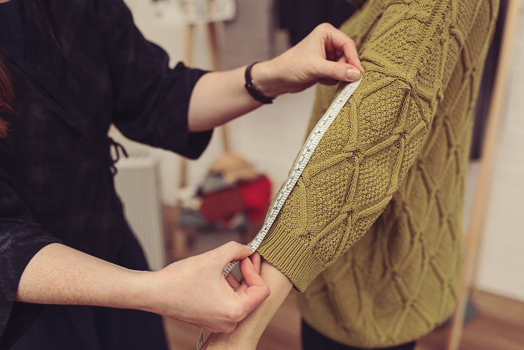 A green OUBAS knitwear jumper is measured to check sizing and finish