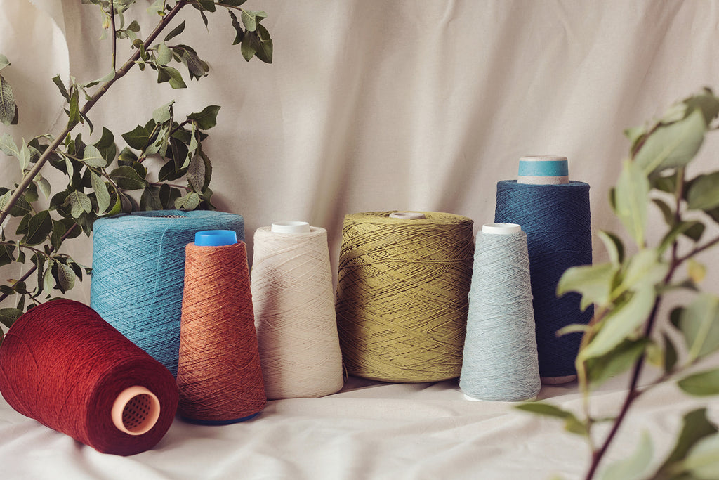 A selection of maroon, blue, pink, cream and green wool yarns against a cream backdrop with natural foliage on either side