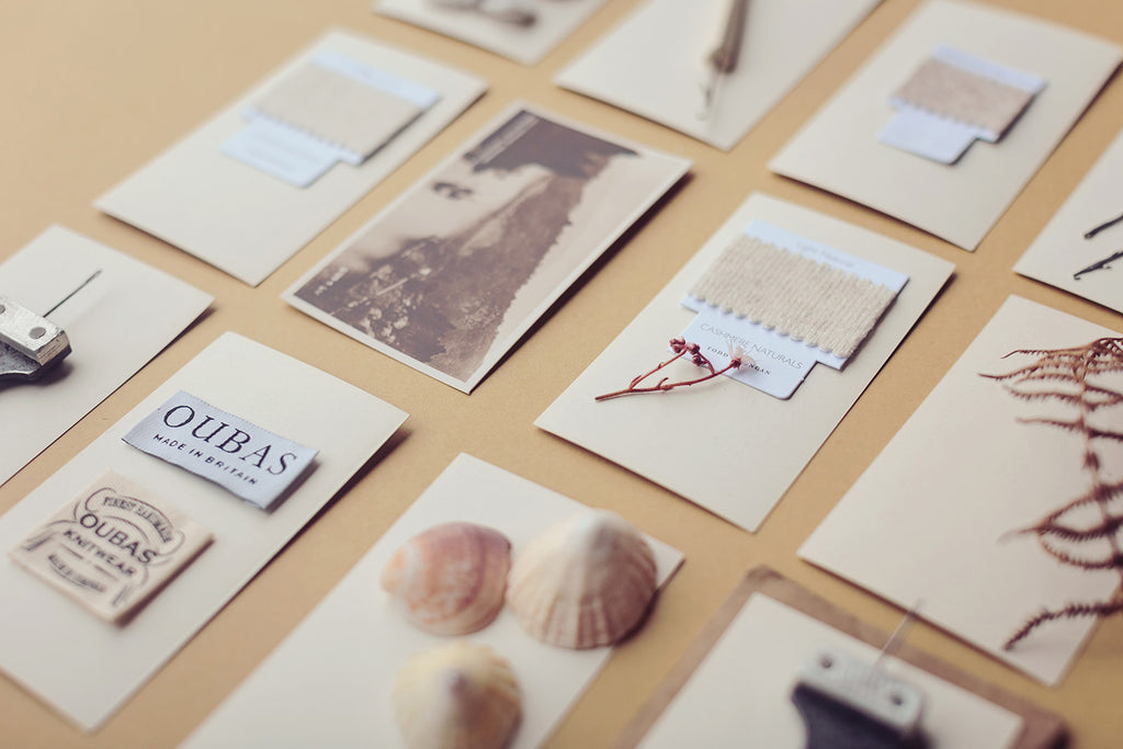 A table showing a selection of old photographs, wool yarn samples, sea shells and foliage placed upon paper cards