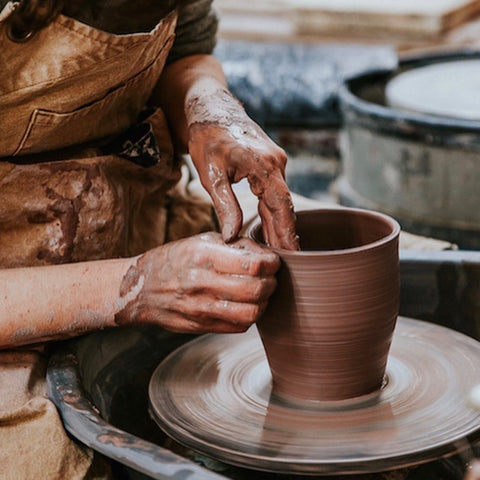 Abigail Schama at work in her ceramics studio, thrown pot on the wheel