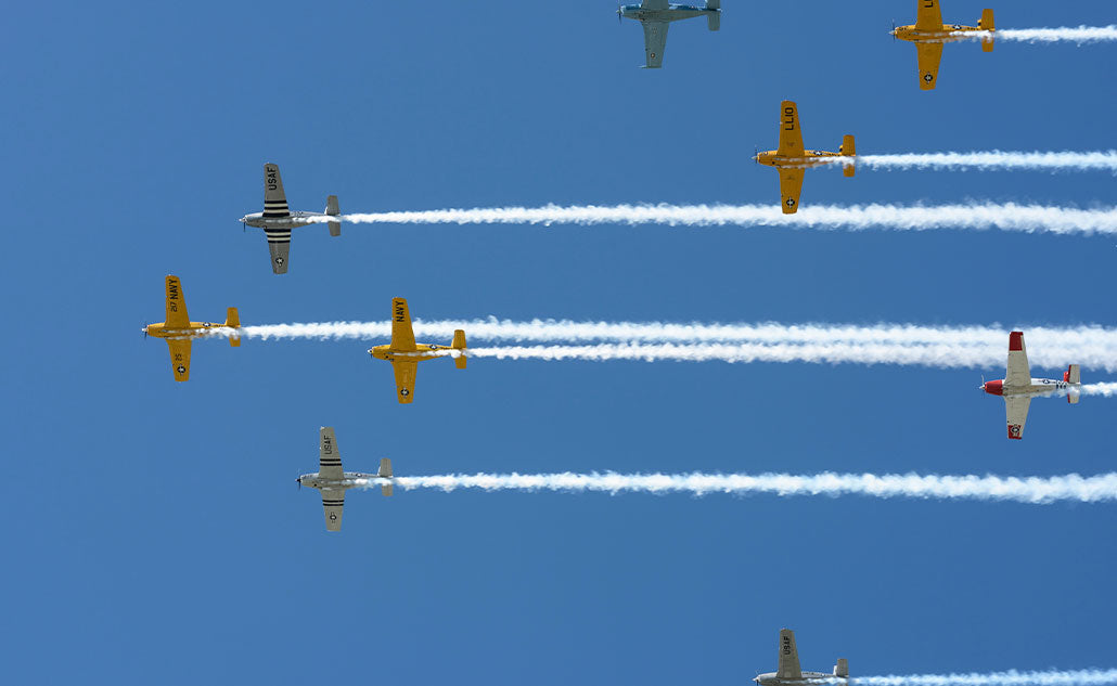 airplanes in sky with trailing clouds