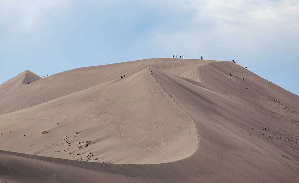 big sand dune with tourists on peak