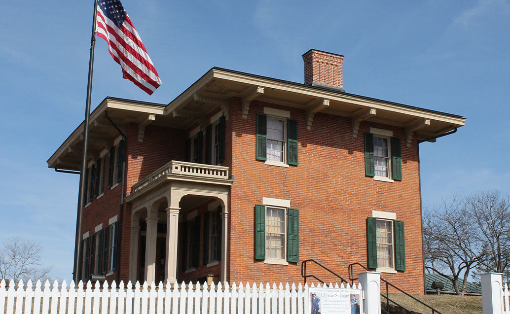 Brick building with white fence and USA Flag
