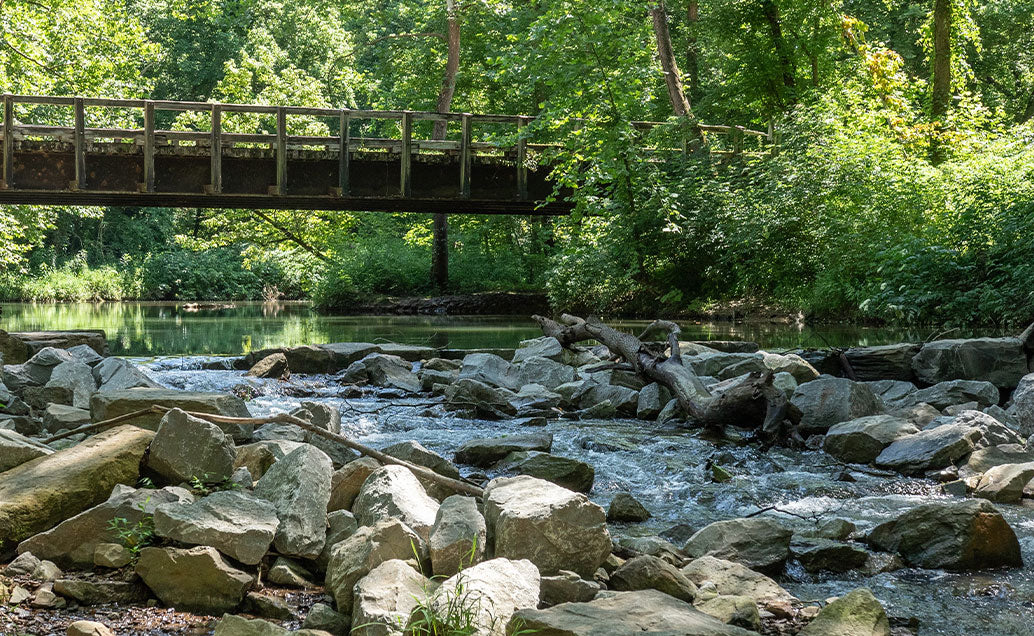 Bridge over river and rocks::River water flows over rocks