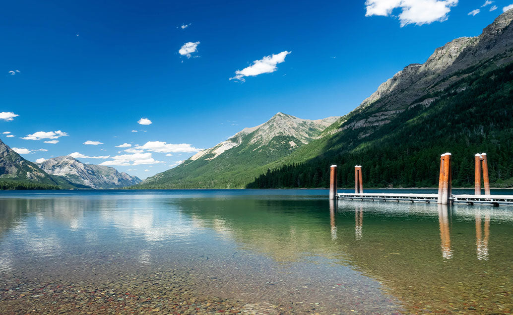 calm lake water by small pier between mountains