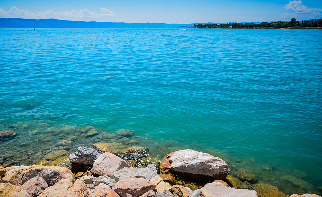 green blue lake view with rocky shore