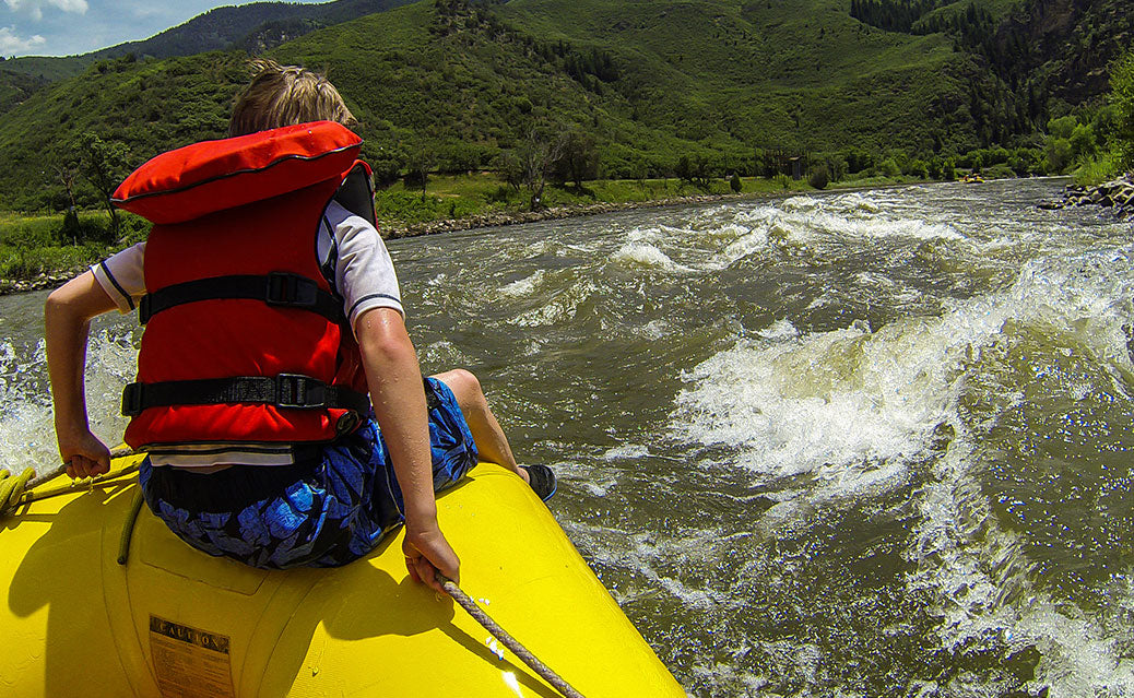 Teen in sitting in front of raft going down the river