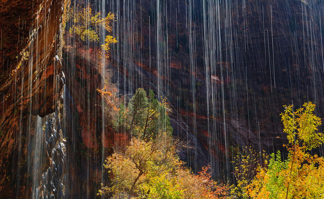 view of light waterfall behind cliff