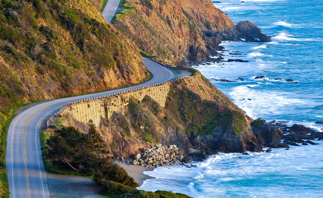 winding mountain road by shore