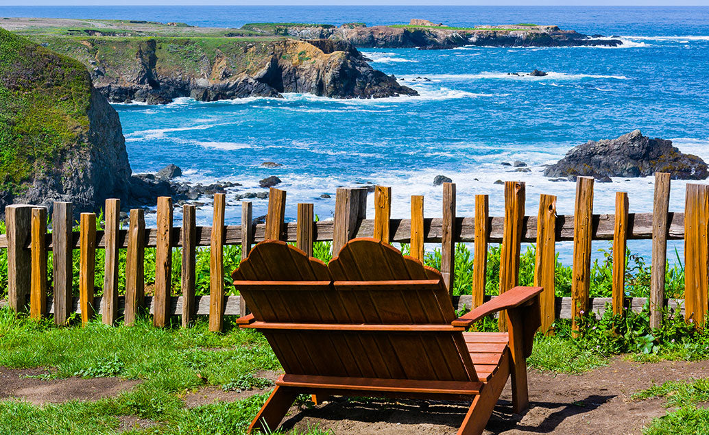 wooden chair on cliff looking to shore