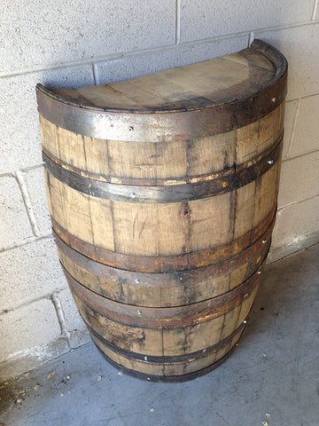 Cradle-cut whiskey barrel placed against a wall. Material Resourcers repurposes materials from industrial & manufacturing companies. Bring us your waste, excess, non-recyclable, by-product, remnant, blemished, cancelled, and expired materials.