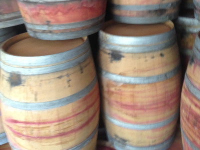 Picture of stacked reclaimed wine barrels. Material Resourcers repurposes materials from industrial & manufacturing companies. Bring us your waste, excess, non-recyclable, by-product, remnant, blemished, cancelled, and expired materials.