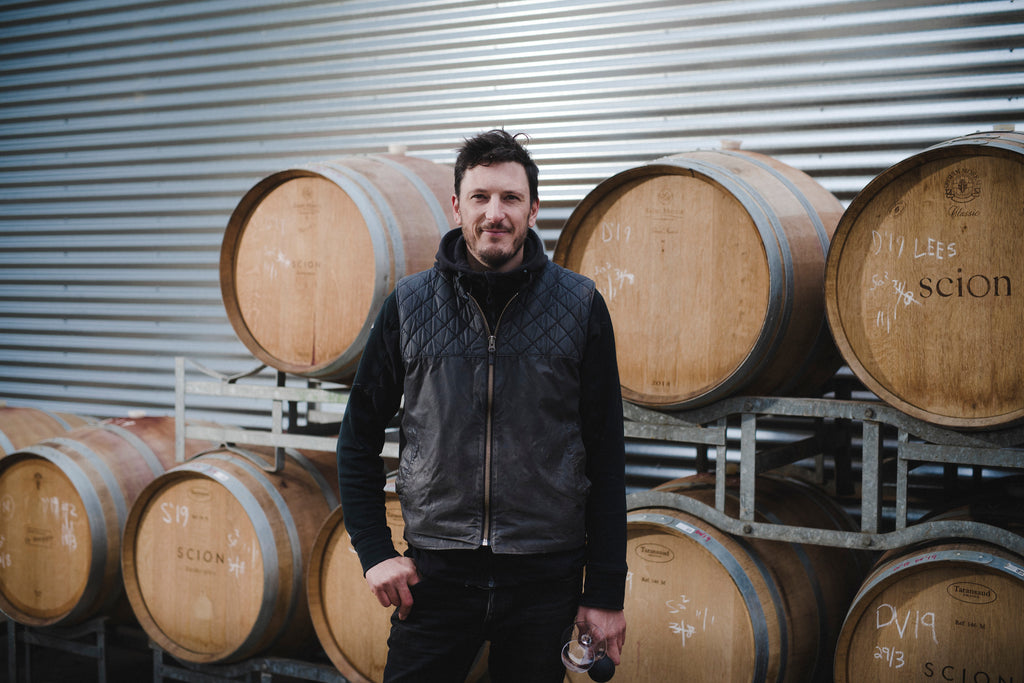 Winemaker Rowly Milhinch standing in front of barrels