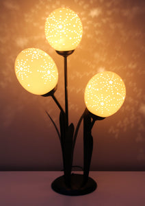 Starburst etched ostrich eggshell set on a flower lamp stand