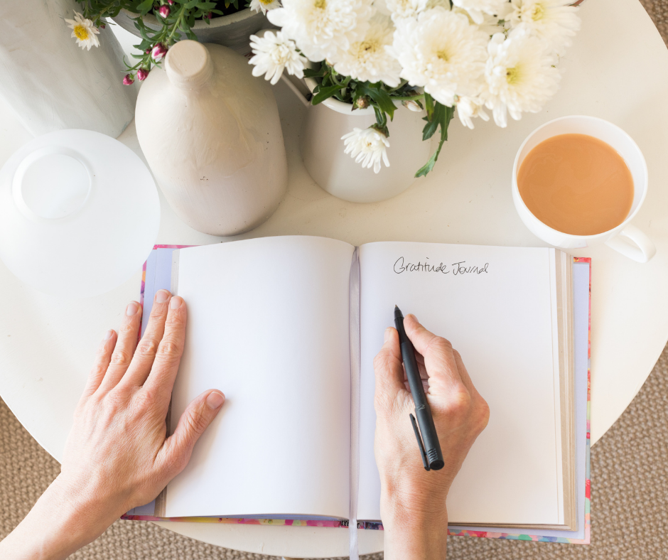 overhead shot of journal on table with woman writing in it
