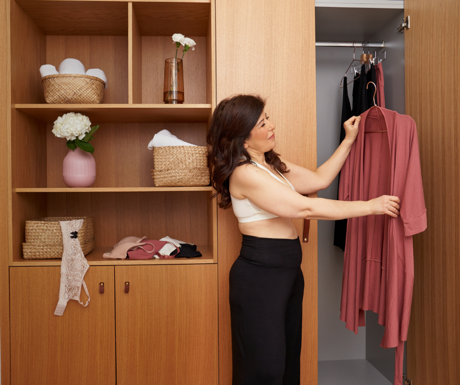 woman in bra and lounge pants holding up a robe on a hanger