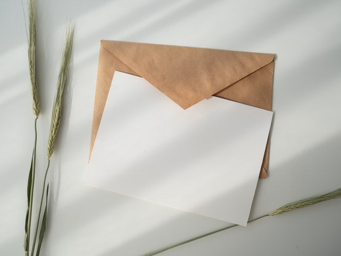 blank white card with brown craft paper envelope behind it