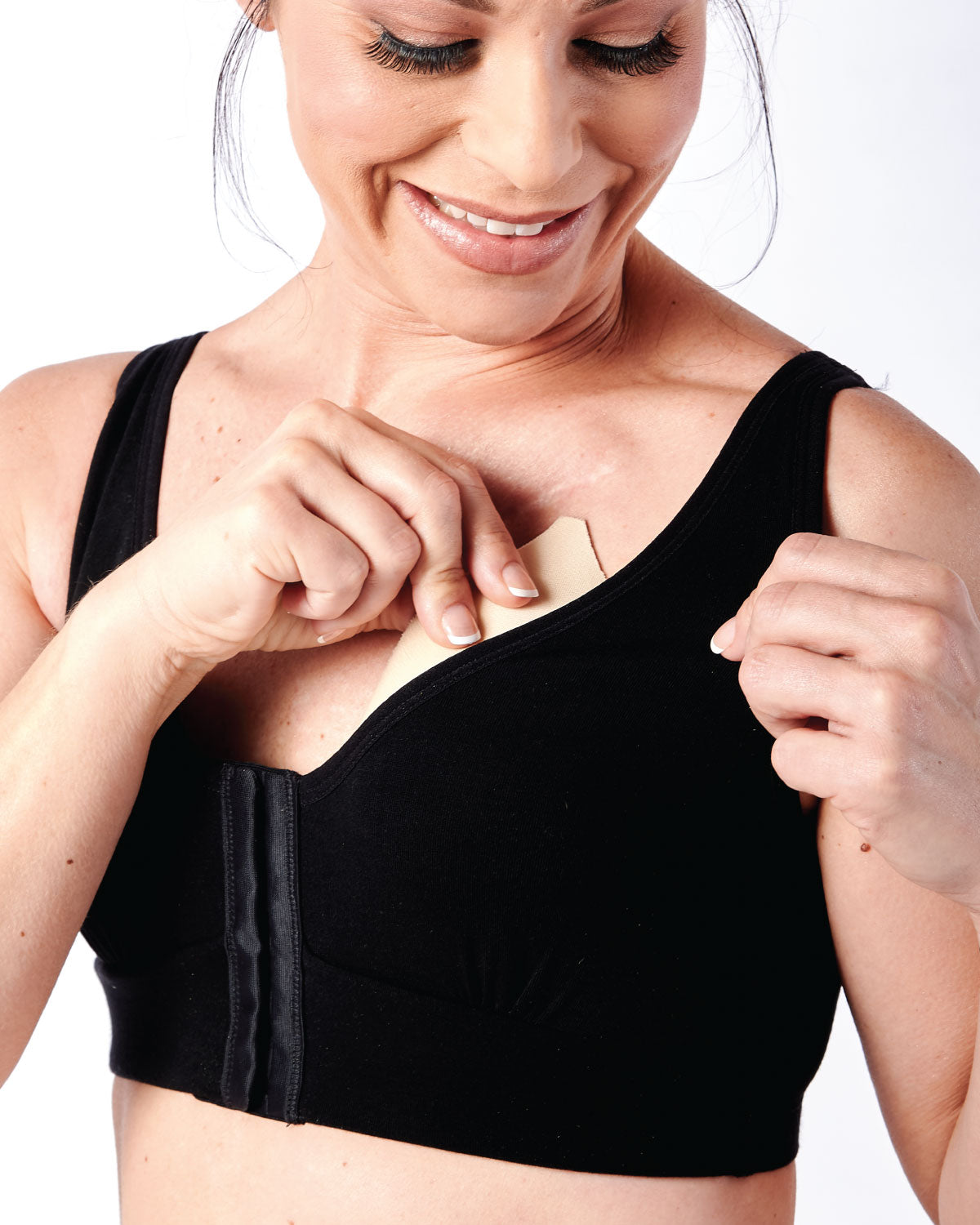 Black, pocketed front closure wireless bra with soft modal material and convertible & adjustable straps on mastectomy model.