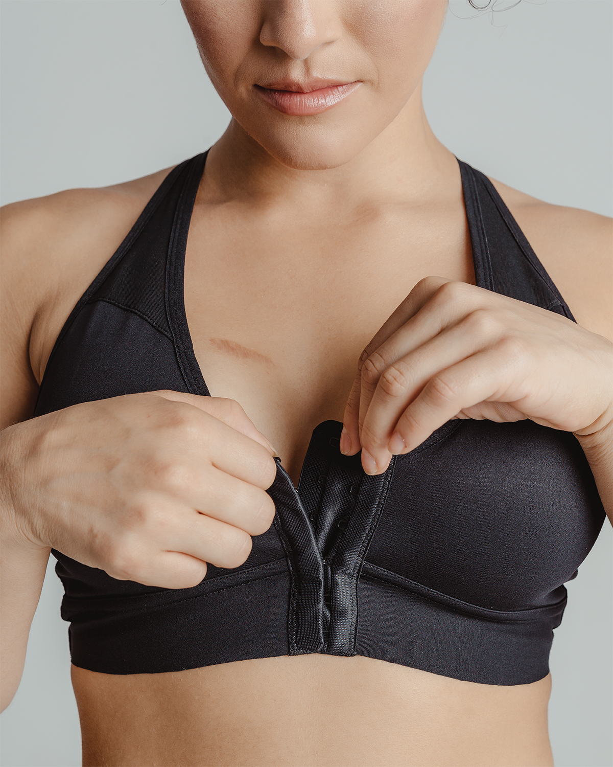 Black, pocketed front closure sports bra with soft wireless cups, adjustable straps and mesh paneling on cross back, on a flap reconstructed model.