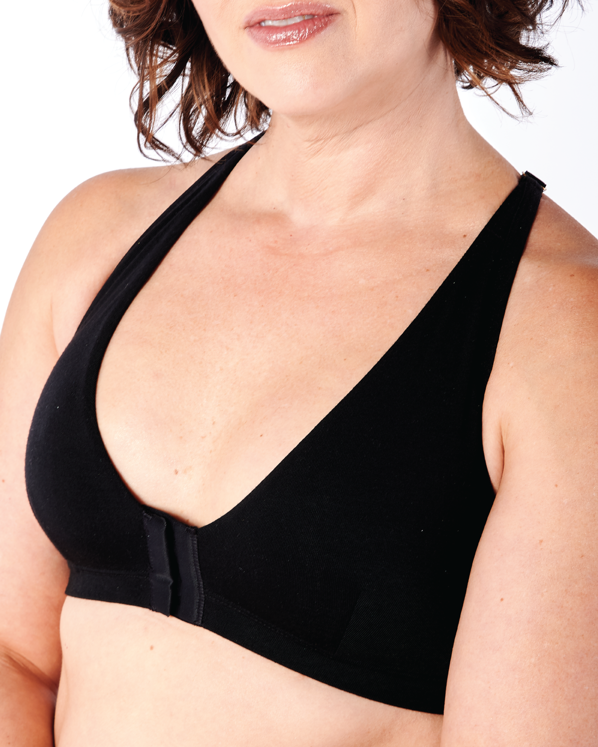 Black, pocketed front closure lace racerback bra with a plunging neckline and soft wire free cups on model with breast implants.