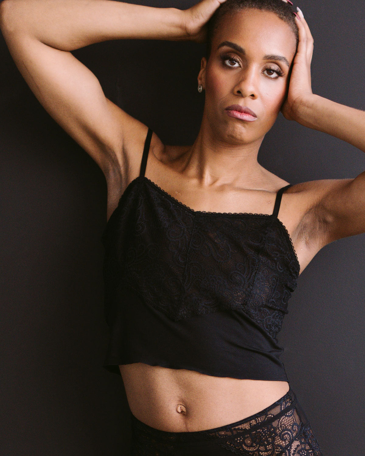 Black, pocketed cropped lace cami with adjustable straps, lettuce hem detail and soft modal on unilateral model.