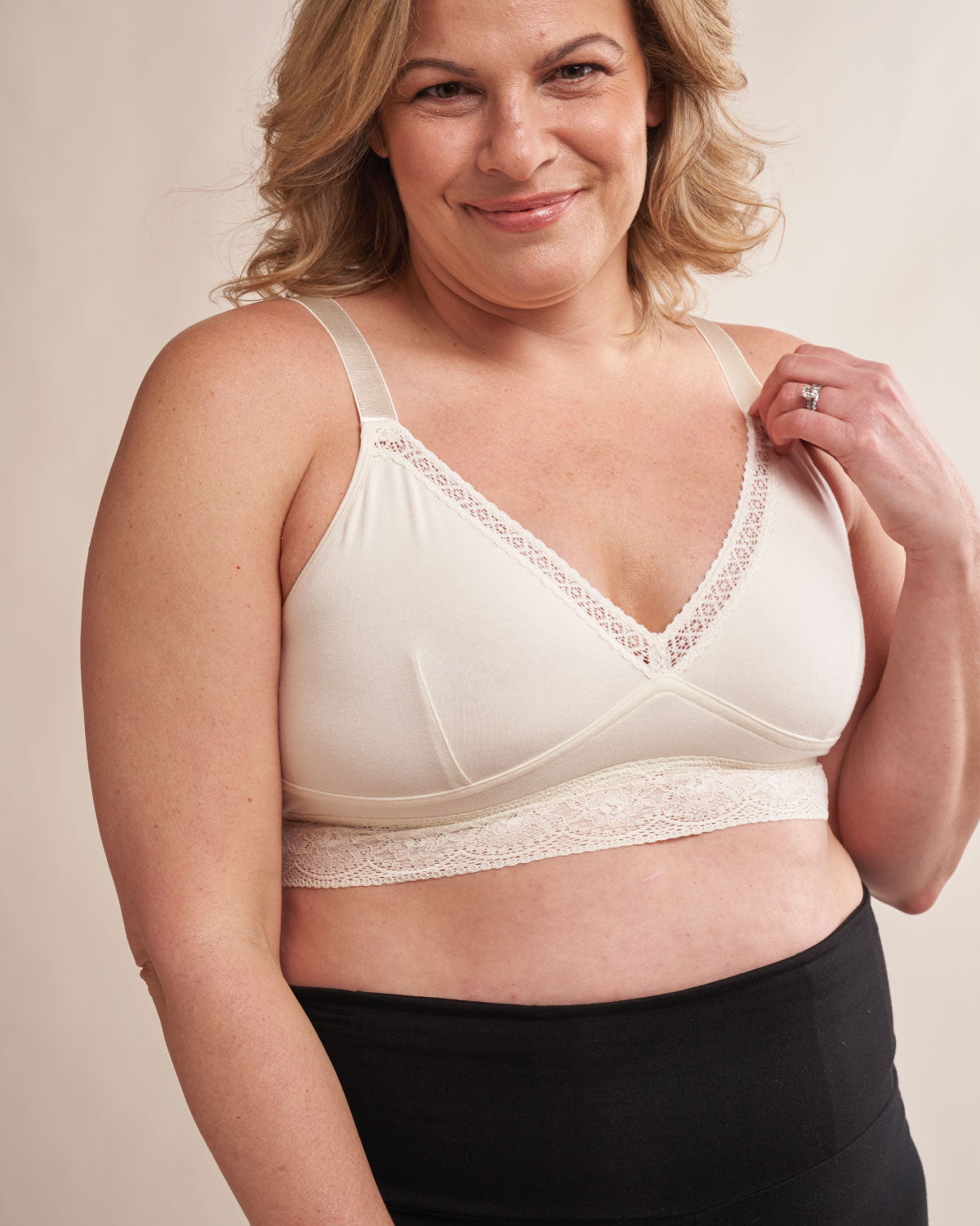 Ivory, longline pullover bra with a lace trim, soft cups, mesh back, adjustable & convertible straps, on a model with breast implants.