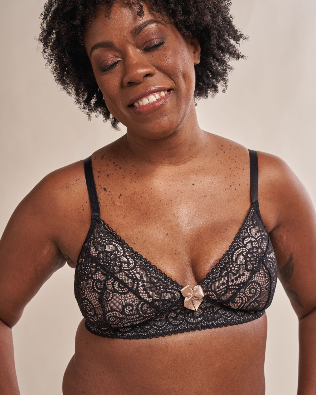Black, pocketed spandex stretch lace bra with fully lined mesh cups, delicate seams, satin bow, back hook closure and adjustable straps, on a flap reconstructed model.